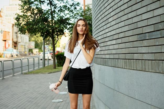 Эмоции, образ жизни, красота, люди, концепция еды-городской портрет молодой привлекательной брюнетки в белой футболке, пьющей молочный коктейль через трубку летом на закате