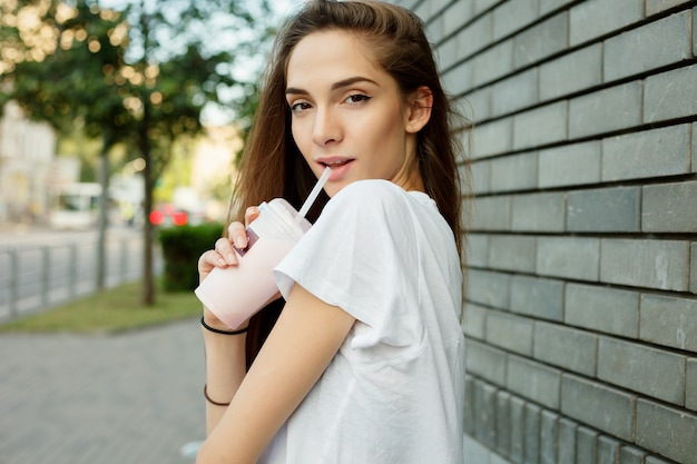 Emotions, lifestyle, beauty, people, food concept-urban portrait of a young attractive brunette female in a white t-shirt drinking milkshake through a tube summer at sunset