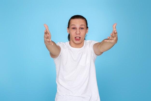 Эмоции телевизионного фаната. крики, ненависть, ярость. плачет эмоциональный сердитый молодой человек кричит на синем фоне. человек, поддерживающий команду