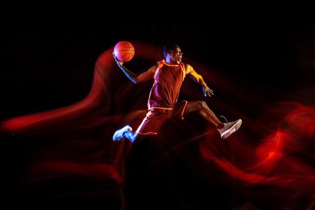 승자의 감정. 어두운 스튜디오 배경 위에 행동과 네온 불빛에 레드 팀의 아프리카 계 미국인 젊은 농구 선수. 스포츠, 운동, 에너지 및 역동적이고 건강한 라이프 스타일의 개념.
