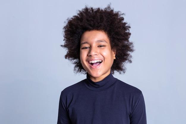 카메라의 감정. 진지한 화보 촬영에 참여하면서 회색 배경에 머물고있는 잘 생긴 긍정적 인 남자 웃음