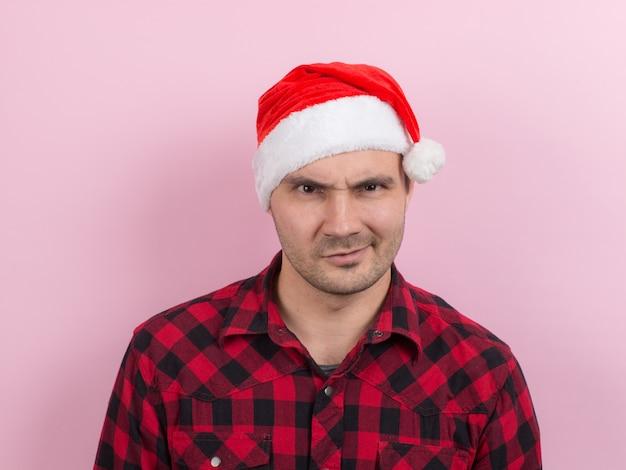 Эмоции на лице, злой, плохой, бандит, заговор зла. человек в клетчатом кролике и рождественской красной шляпе