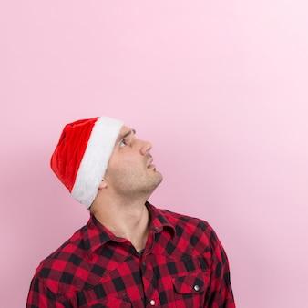 Эмоции на лице, страх, праздничные воспоминания, негатив. человек в клетчатом кролике и рождественской красной шляпе