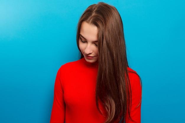 감정, 사람, 아름다움, 패션 및 라이프 스타일 개념 - 뷰티 패션 초상화. 파란색 벽 배경에 웃는 젊은 여자.
