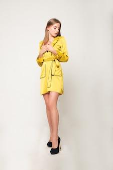 감정, 사람, 아름다움, 패션 및 라이프스타일 개념 - 젊고 멋진 여성의 패션 사진. 노란색 밝은 드레스, 목욕 가운 . 포즈를 취하는 소녀. 스튜디오 사진