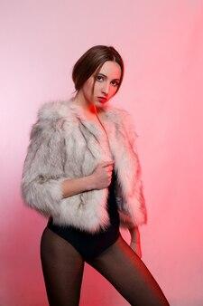 感情、人、美しさ、ファッション、ライフスタイルのコンセプト-赤い背景に人工毛皮の灰色の毛皮のコートを着たファッショナブルな美しい女性は眉をひそめている