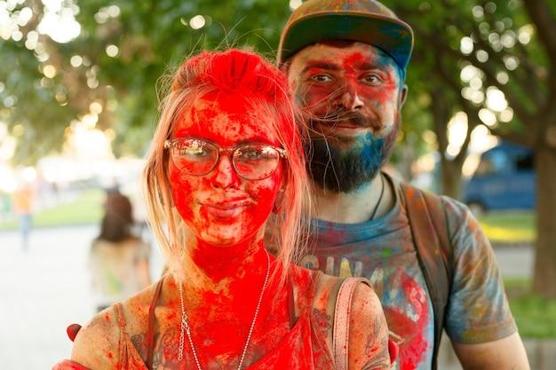 感情、人、美しさ、ファッション、ライフスタイルのコンセプト-ホーリーのカラフルな祭りを祝うペイントされた顔を持つセルフィー写真の観光客のカップル