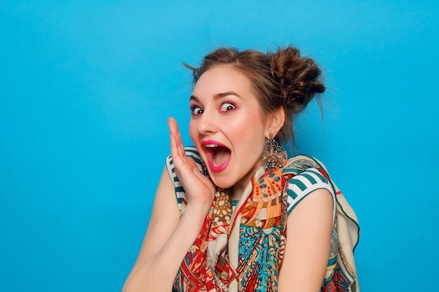 感情、人、美しさ、ファッション、ライフスタイルの概念-青い背景の上に、ショックを受けた表情を持つ若い女性の肖像画