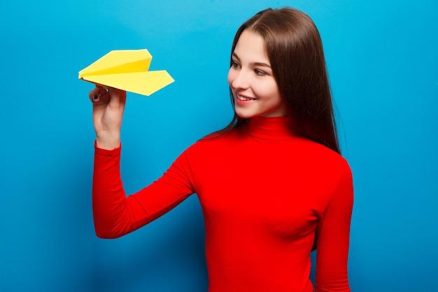 감정, 사람, 아름다움, 패션, 라이프스타일, 여행, 관광, 그리고 사람들의 개념 - 노란 종이 비행기를 들고 있는 아름다운 여성의 초상화. 파란색 배경에.