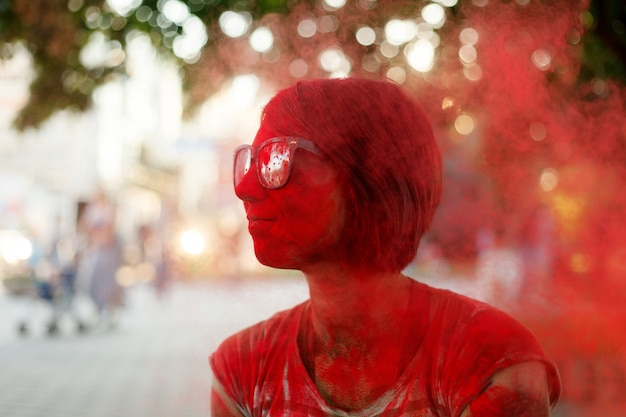 Emotions, people, beauty, fashion and lifestyle concept - portrait of a beautiful girl full of colored powder all over the body