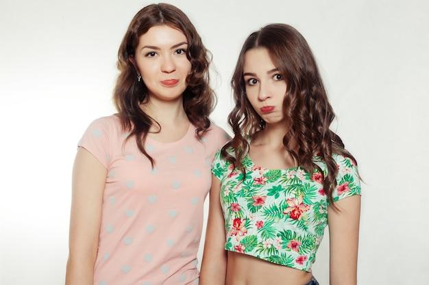 感情、人々、十代の若者たちと友情の概念-灰色の背景に抱き締める幸せな笑顔のかわいい十代の少女や友人