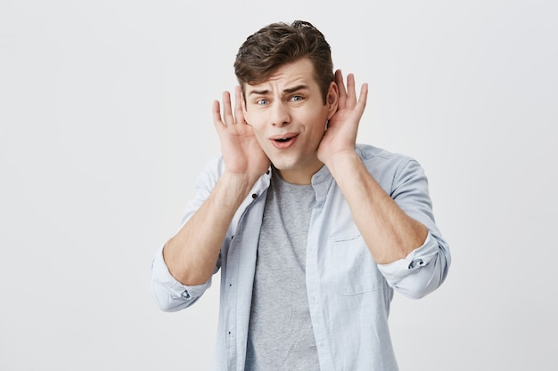 Emotions, reaction, face expressions concept. handsome shocked puzzled european male keeps opened palms behind ears, keeps mouth widely opened, being in stupor, not believing in words he heard.