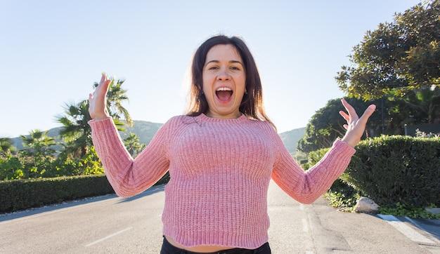 感情、夏と幸福の概念-自然のカジュアルな服を着て面白い若い女性を笑う。