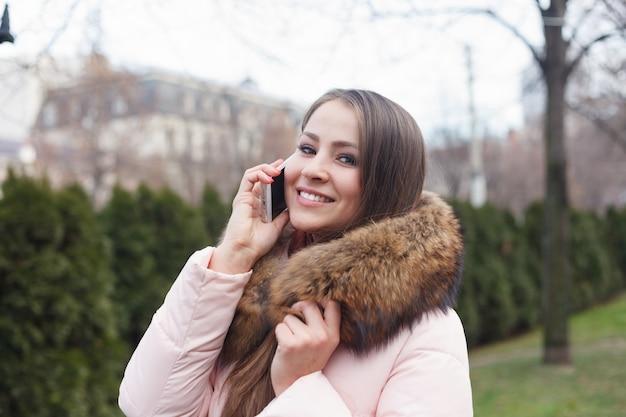 감정, 기술 및 사람들 개념-웃는 젊은 여자 또는 십 대 소녀 문자 메시지 스마트 폰. 스마트 폰에 음성 메시지를 말하는 거리에 걷는 여자. 전화 통화. 메시지를 쓴다