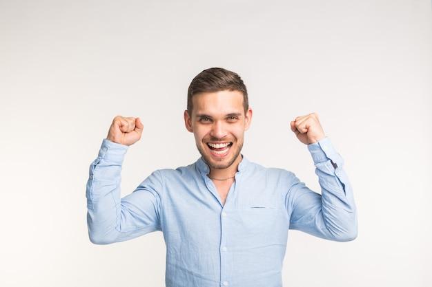 Эмоции, победа и концепция людей - радостный красавец с поднятыми руками над белой поверхностью