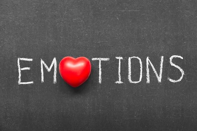 Слово эмоции, написанное от руки на доске с символом сердца вместо o