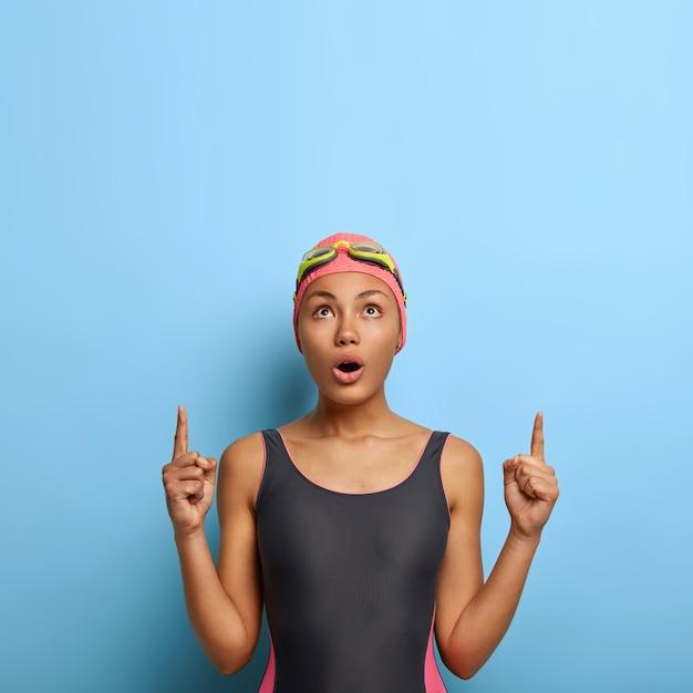 Emotiva donna atletica in costume da bagno nero e cuffia da bagno