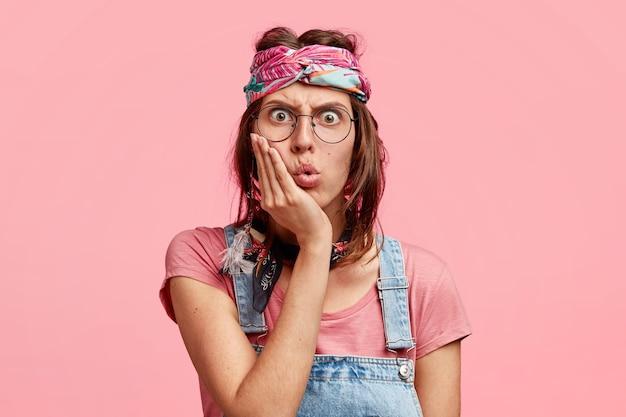 Emotiva bella donna hippie tiene la mano sulla guancia, guarda con espressione perplessa sorpresa alla telecamera, aggrotta le sopracciglia con rabbia