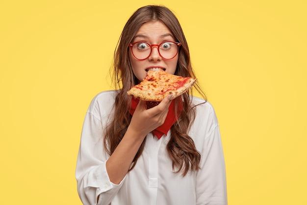 Эмоциональная красивая дама кусает вкусную пиццу, смотрит прямо, успевает перекусить, посещает пиццерию, удивлена низкими ценами, моделями у желтой стены. люди, фастфуд и питание
