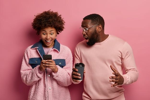 感情的な黒人女性と男性がスマートフォンデバイスを見つめ、素晴らしいニュースに反応し、メッセージを受け取り、テイクアウトコーヒーを飲みます