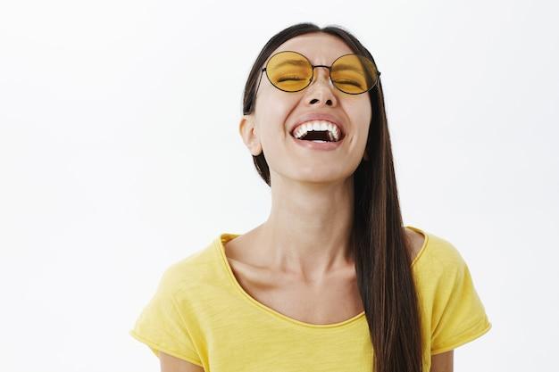 笑いながら頭を持ち上げる丸い黄色のサングラスで黒髪の感情的なのんきで明るい魅力的な女性