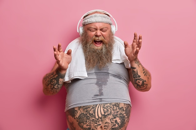 Emotive chubby hipster listens music in headphones, sings song loudly, dressed in sports wear, has fitness training to loose weight, poses against rosy wall. athlete thick bearded man indoor