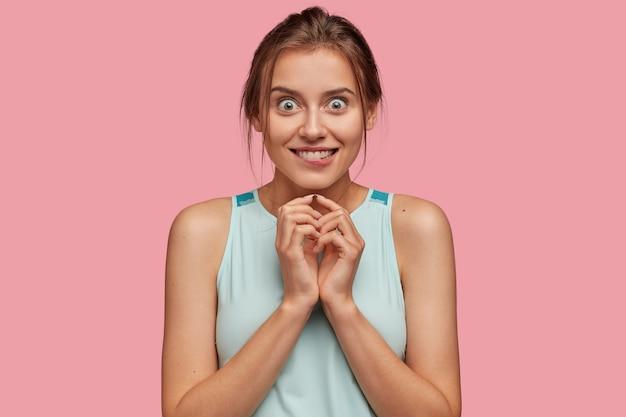 Эмоциональная, любопытная жизнерадостная женщина ожидает чего-то приятного, кусает губы, имеет зубастую улыбку, держит руки на груди, смотрит большими глазами, одетая в повседневную одежду, изолирована за розовой стеной