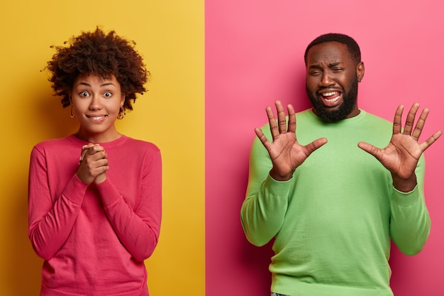 Emotive curly haired woman keeps hands together, gazes with anticipation, going to hear important results, displeased bearded man raises palms, discontent with something, poses over vibrant wall