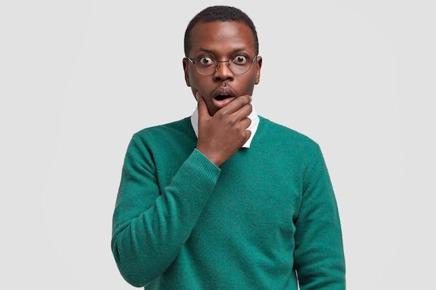 Эмоциональный темнокожий мужчина держит руку за подбородок, смотрит с озадаченным испуганным выражением лица, обеспокоен от удивления.
