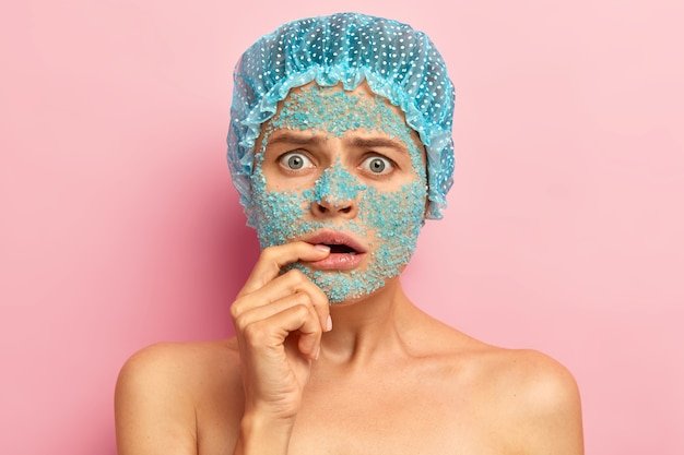 Emotive dissatisfied woman looks with unhappy expression, keeps fore finger on lips, hears bad news from beautician, applies nourishing blue sea salt mask