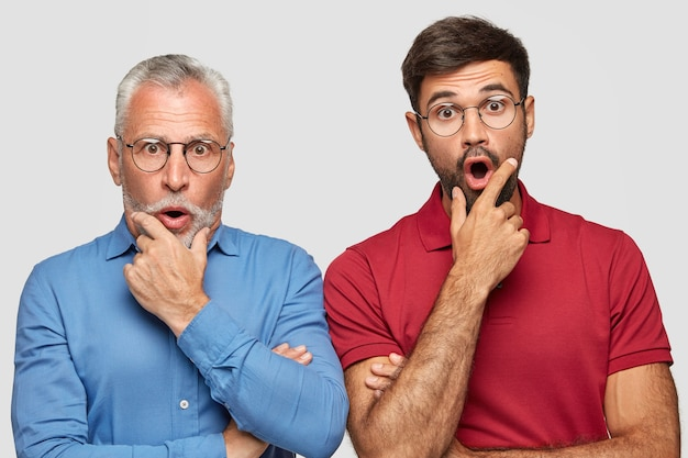 Emotive elderly father and son have shocked faces, hold chins, drop chins with surprisement, recieve unexpected news, pose against white wall. people, generation, emotions and reaction concept