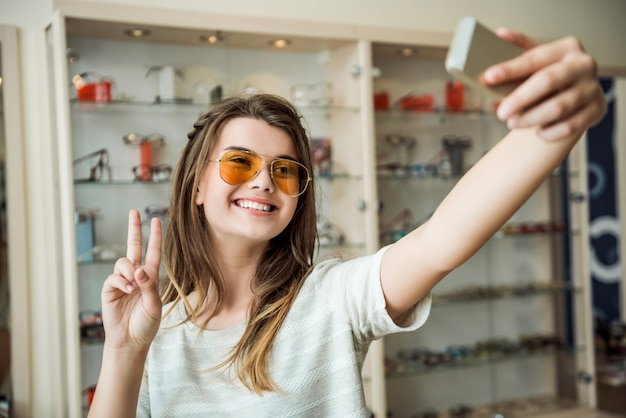 Emotive fashionable urban woman in optician store standing over stands with glasses while taking selfie in stylish sunglasses