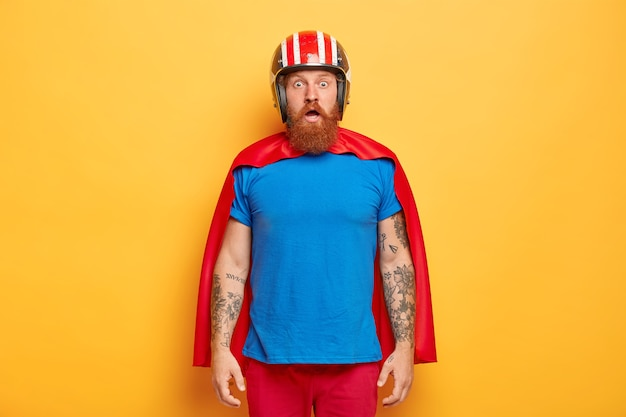Emotive ginger bearded man wears protective helmet, red cloak and blue t shirt