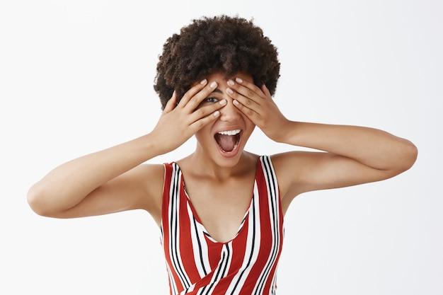줄무늬 복장을 한 감정적 인 잘 생긴 아프리카 여성, 행복하고 즐거운 느낌, 손바닥으로 눈을 가리고 손가락으로 엿보기, 미소 짓기, 회색 벽 너머로 엿보기
