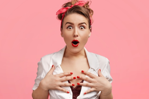 感情的なゴージャスな女性は胸に手を保ち、バグのある目と息を切らして見つめ、素晴らしいものを信じることができず、赤いヘッドバンドを身に着け、赤い塗装の唇とマニキュアを持ち、ピンクで隔離されています