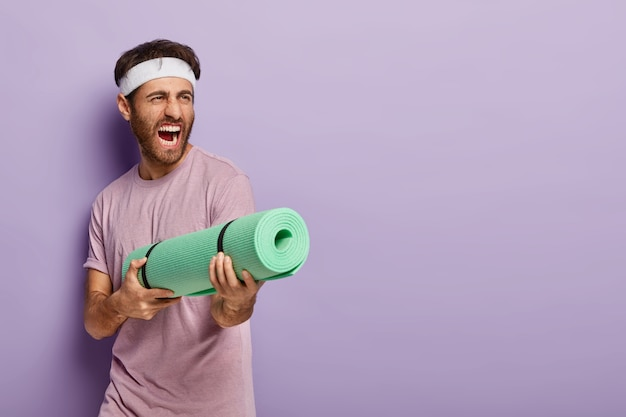 Emotive handsome man pretends shooting in someone with fitness mat, screams loudly