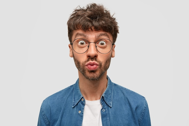Эмоциональный красивый молодой парень изумленно надувает губы, смотрит через большие очки, с темной щетиной, одет в джинсовую рубашку, позирует на фоне белой стены