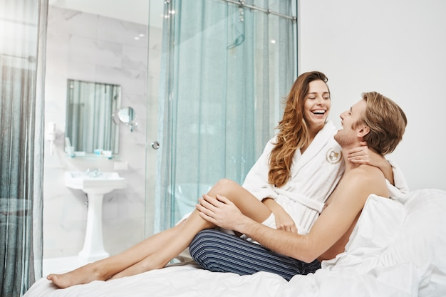 Emotive happy european couple laughing and cuddling while sitting in hotel bedroom in daytime, wearing pyjamas and bathrobe. two cute lovers making fun and joking being in great mood.