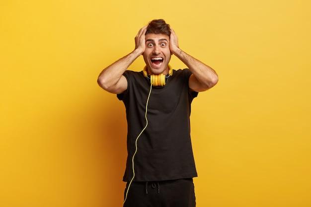 감동적인 행복 놀란 남자는 머리에 손을 얹고 눈을 곤두 세우고 눈을 크게 뜨고 놀라운 것을 믿을 수 없습니다.