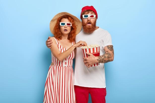 感動的なショウガのカップルがポップコーンを抱きしめて食べ、映画館で怖い映画を見る