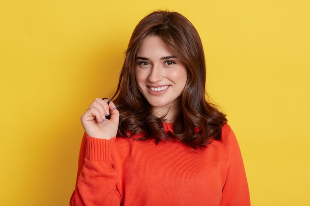 Emotive playful european girl in casual outfit holding hair while and smiling sensual, flirting isolated over yellow wall, being satisfied, has good mood.