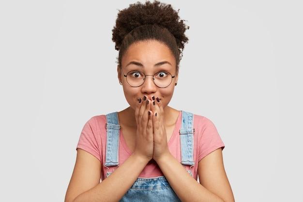 眼鏡をかけた感情的に喜ばれる暗い肌の女性は、両手で口を覆い、信じられないほどの何かを見て、くしのある髪をくっきりさせ、白い壁にモデルを作ります