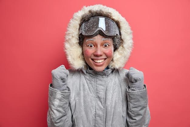 La donna emotiva positiva alza i pugni e non vede l'ora che lo snowboard esprima emozioni felici, gode del periodo invernale e del riposo attivo indossa una giacca calda e occhiali da sci. sciatore femminile allegro