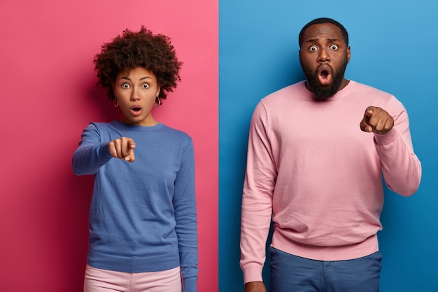 Emotive scared afro american woman and man point index fingers at you wear colorful clothes react on something terrifying, stand in studio against pink