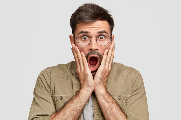 Emotive scared shocked male with widely opened mouth hears impressive rumor, stares with stunned expression, being in stupor, wears round glasses, isolated over white wall