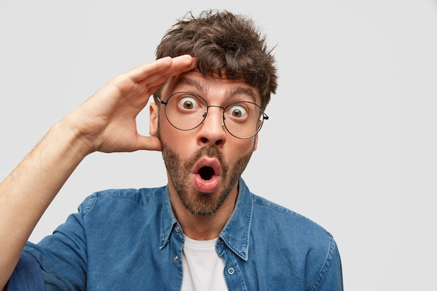 감정적 인 충격을받은 수염 난 남성은 도청 된 눈으로 응시하고, 머리에 손을 대고, 불신을 표현하고, 흰 벽 위에 고립 된 자장 반응을 보입니다.