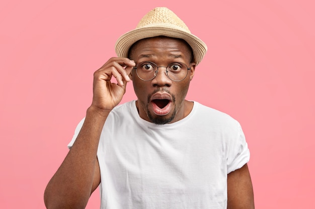 Emotive stunned young man opens mouth and stares through glasses, being shocked by latest news, wears fashionable straw hat, stands alone against pink wall