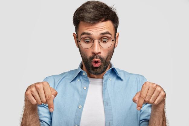 驚いた表情の感情的な愚かな若い男性は、両方の人差し指で下を向いて、何か奇妙なことに気づき、目を飛び出させ続け、カジュアルな服を着て、白い壁に隔離されます