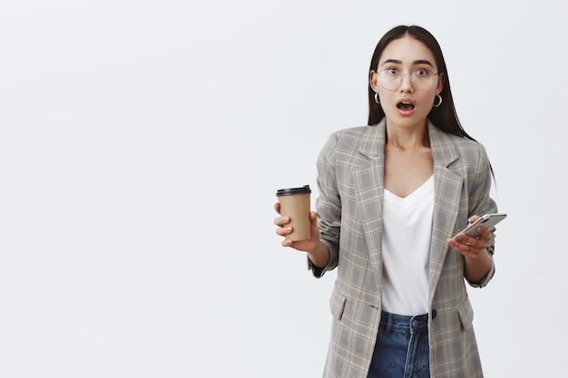 재킷과 안경에 감동적인 세련된 여성 학생, 스마트 폰과 커피 한잔 들고 놀라움과 이야기