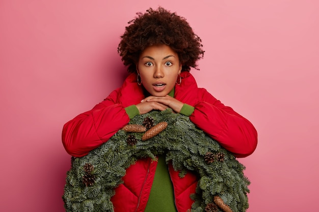 Emotive surprised curly haired woman leans at green handmade wreath with cones, expresses wonder, dressed in red coat, isolated over pink background